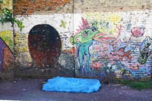 Homeless man infront of street art buenos aires