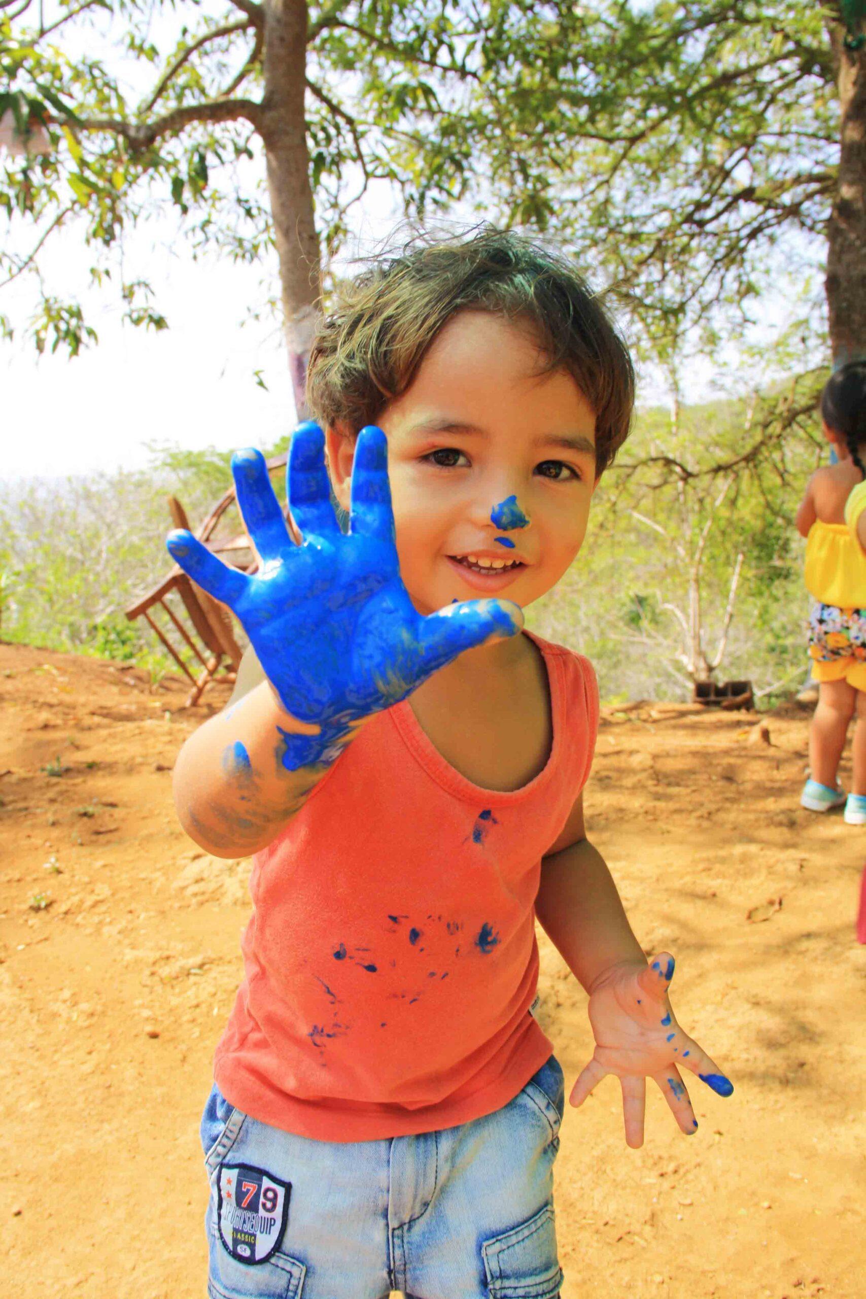 Boy painting at elementary school Mi Casa en Ipauratu
