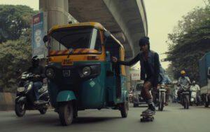 Indian skate culture woman riding on skateboard while holding on tuk tuk