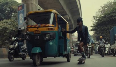 Indian skate culture woman riding on skateboard while holding on tuk tuk