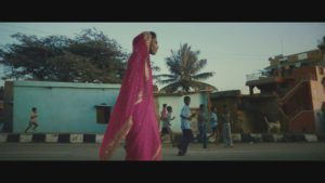 Indian girl skateboarden in pink saree