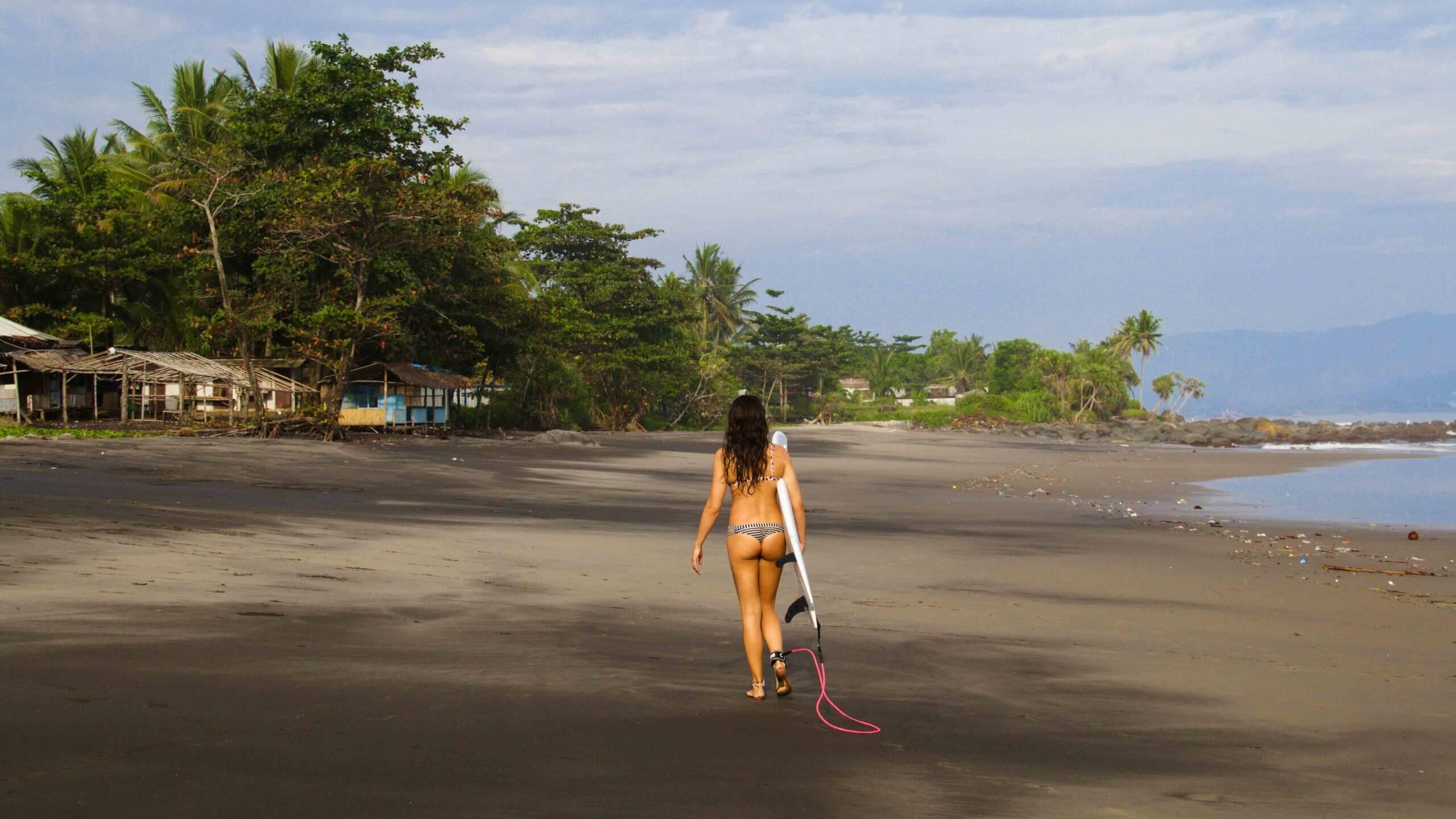 Surfer girl on Cimaja beach Java