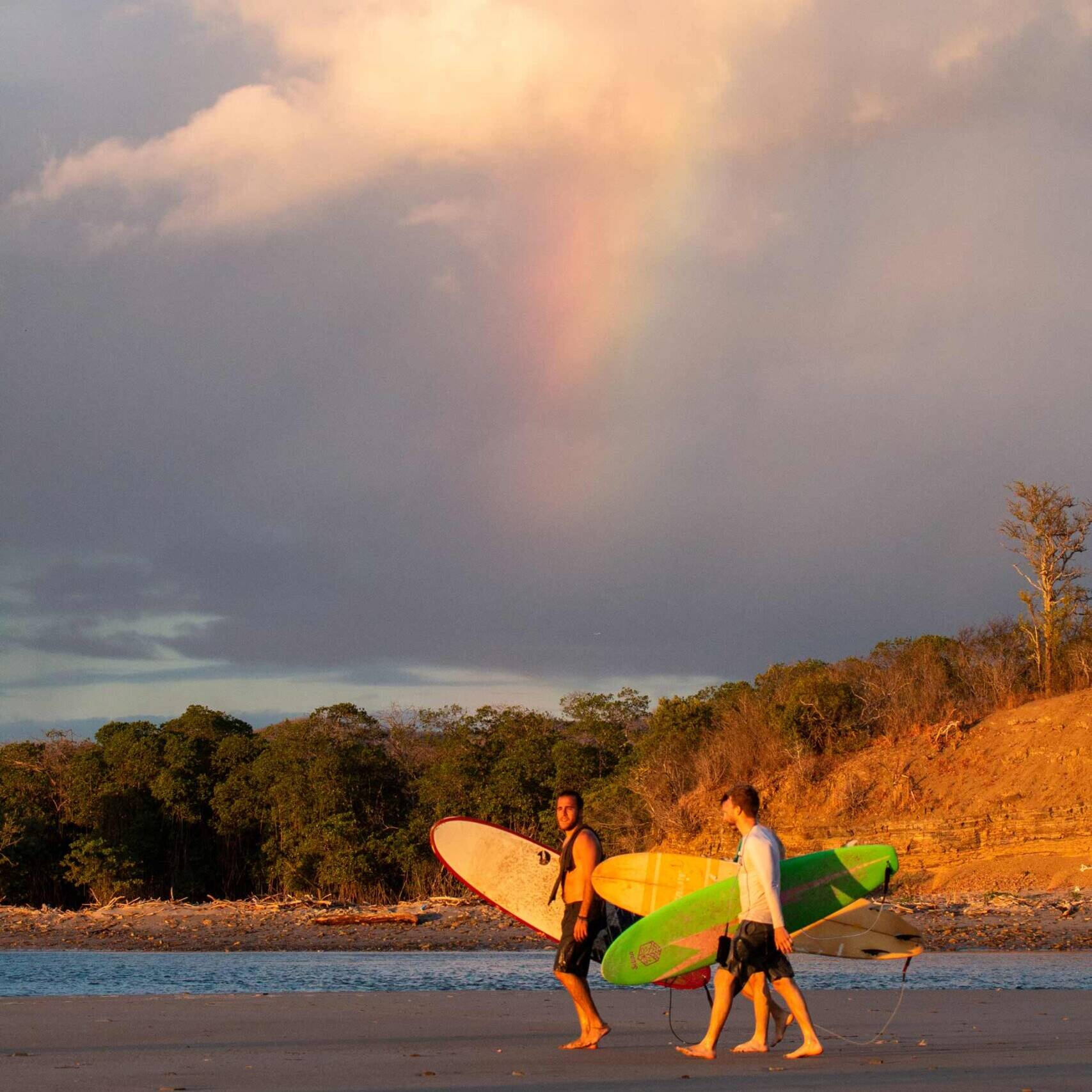 Surfers under the rainbow at Playa Popoyo Nicaragua