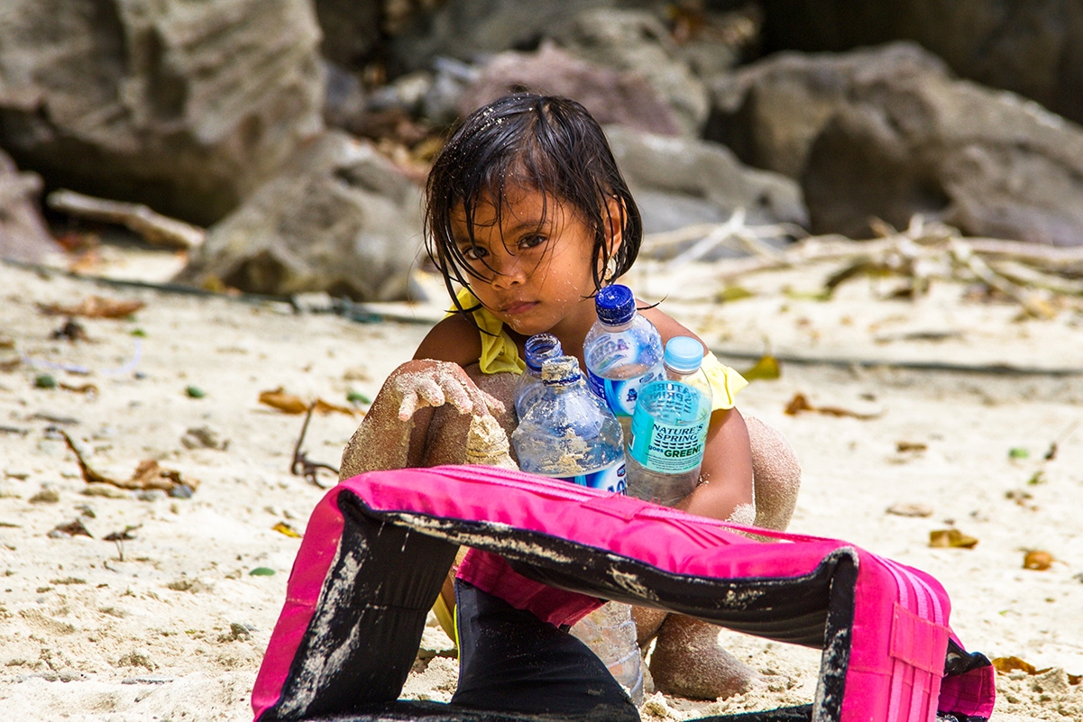 Girl on the beach with plastic bottles in Sumatra