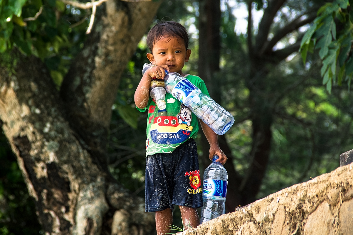 Boy on the beach with plastic bottles in Sumatra