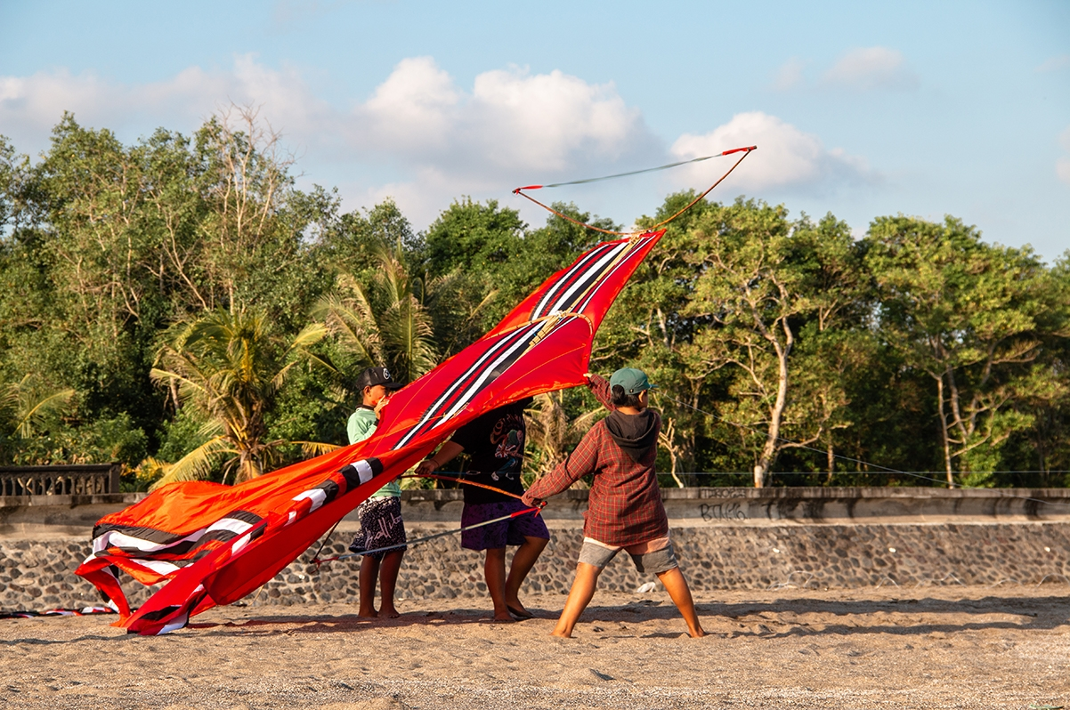 Local boys kiting on the beach in Bali