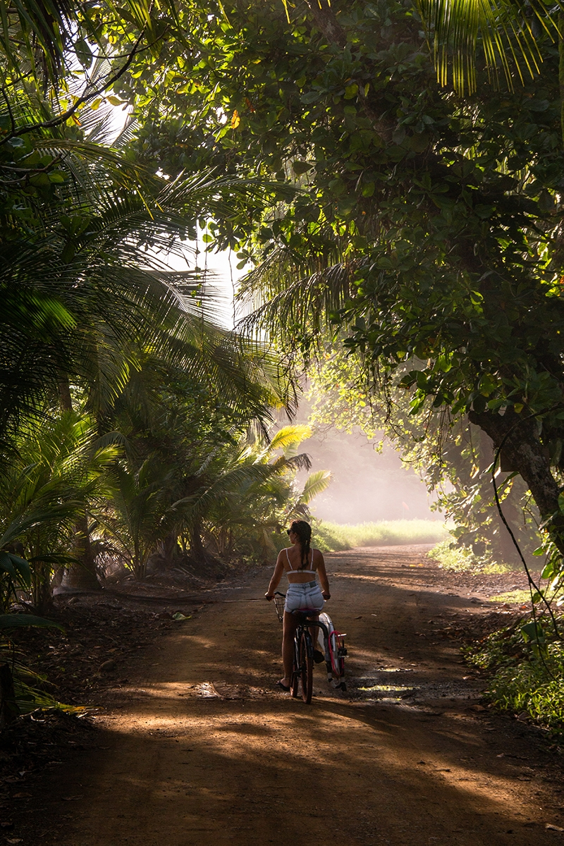 Surfer girl on a bicycle in Punta Banco Costa Rica
